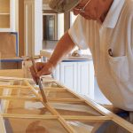 A painting contractor primes kitchen cabinets before repainting