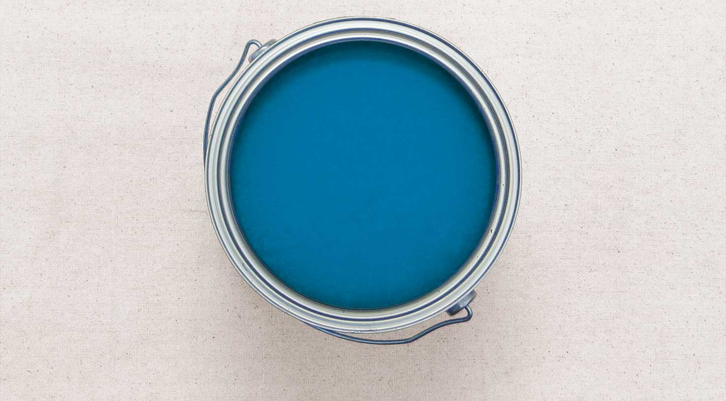 Aeial view of an open gallon can of bright blue paint