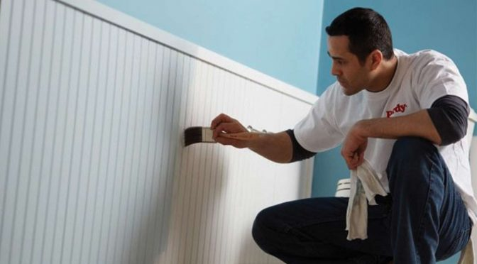a contractor painting interior wainscoating