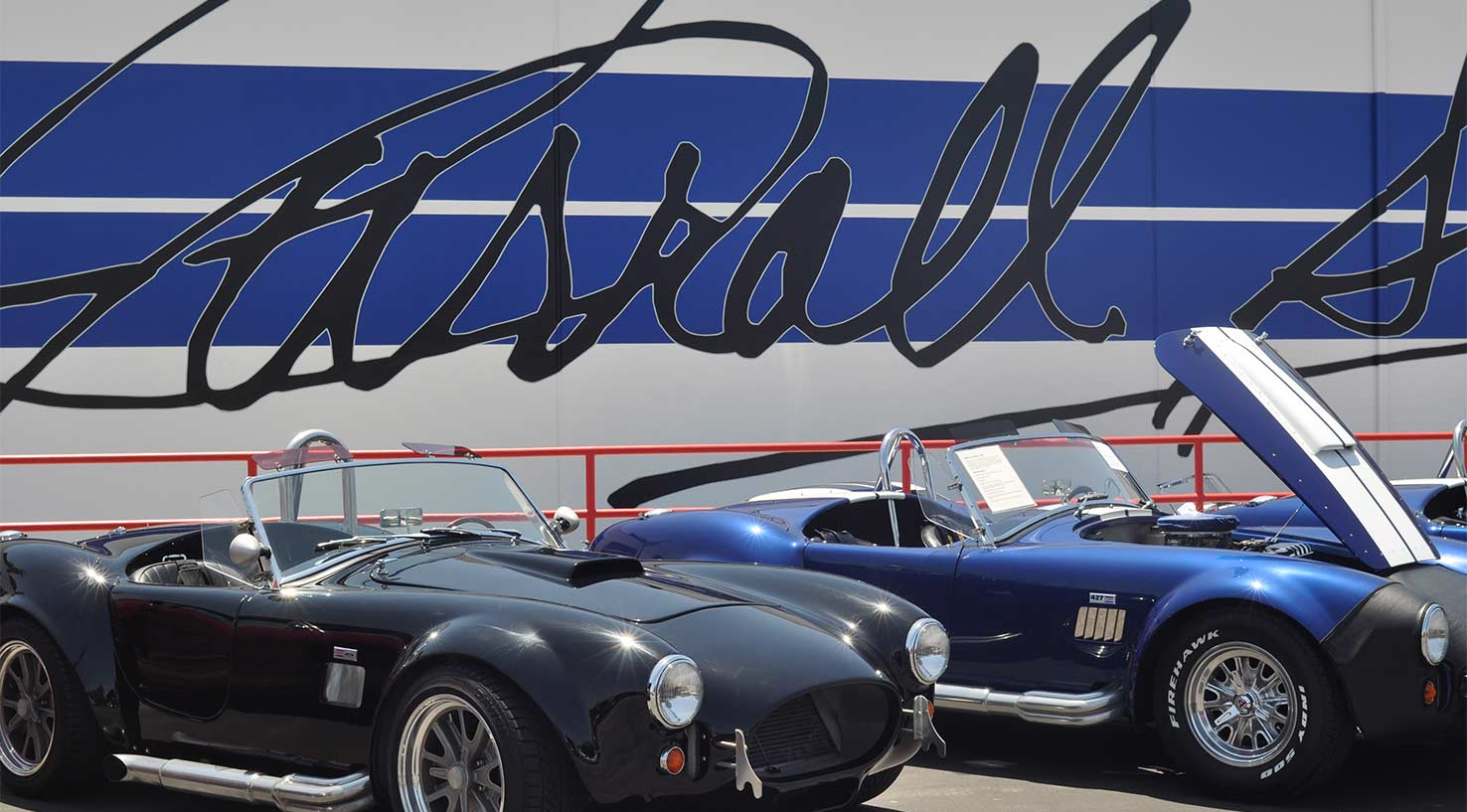 Several Shelby Cobras in front of the newly repainted car company's corporate headquarters