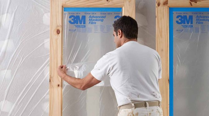 painter masking a doorway with plastic film