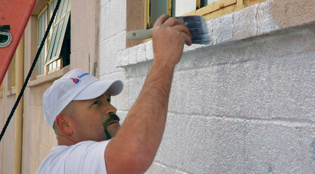 painter priming exterior concrete block