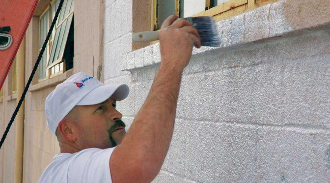 painter priming exterior concrete block