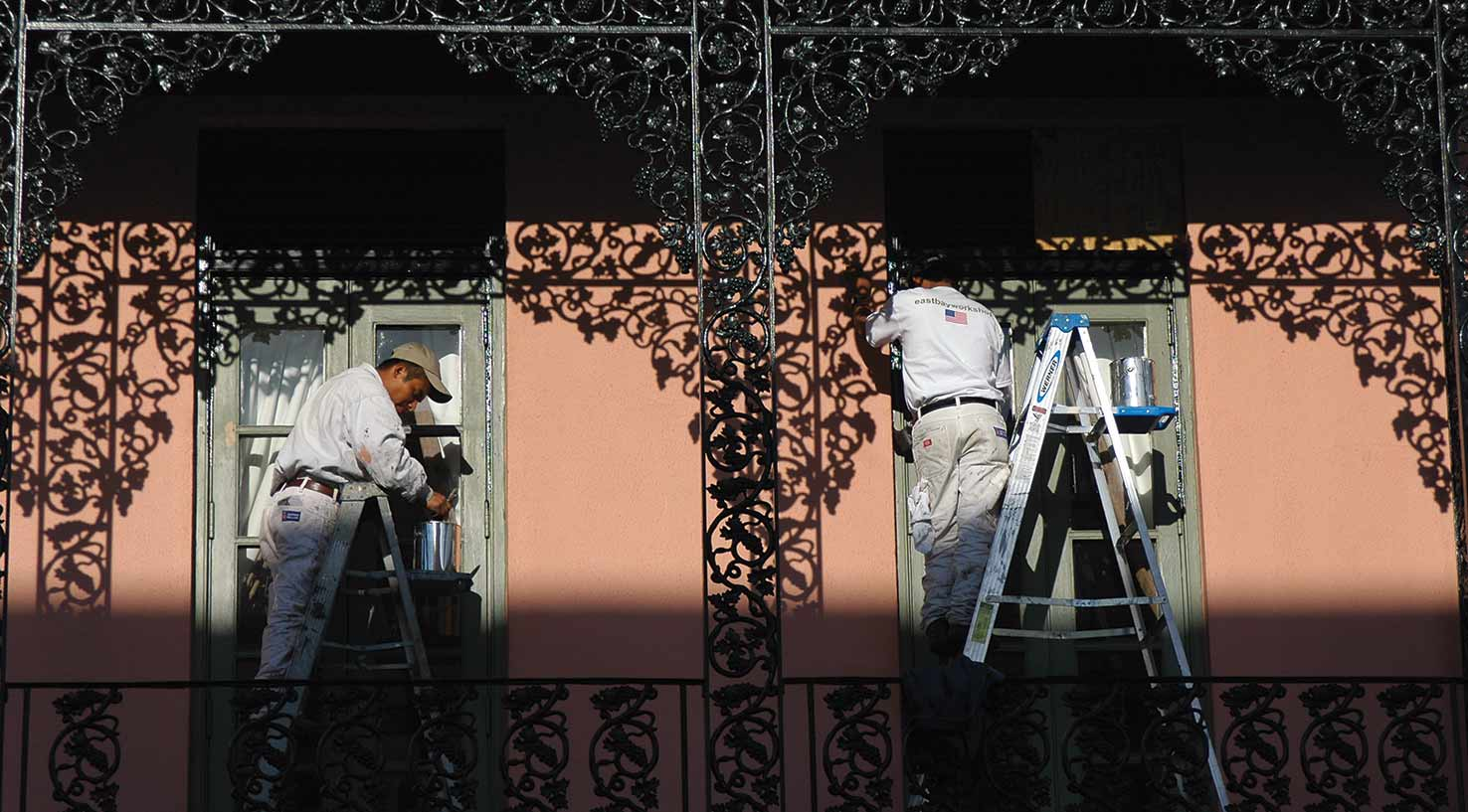 Two painters apply enamel to the exterior windows of a hotel in New Orleans