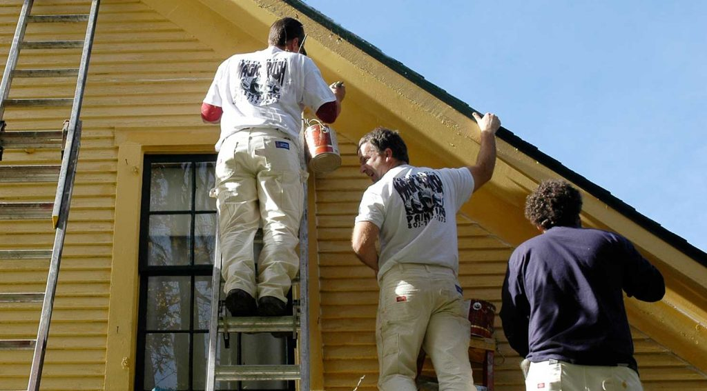 A three-man paint crew topcoats a wood-sided home exterior